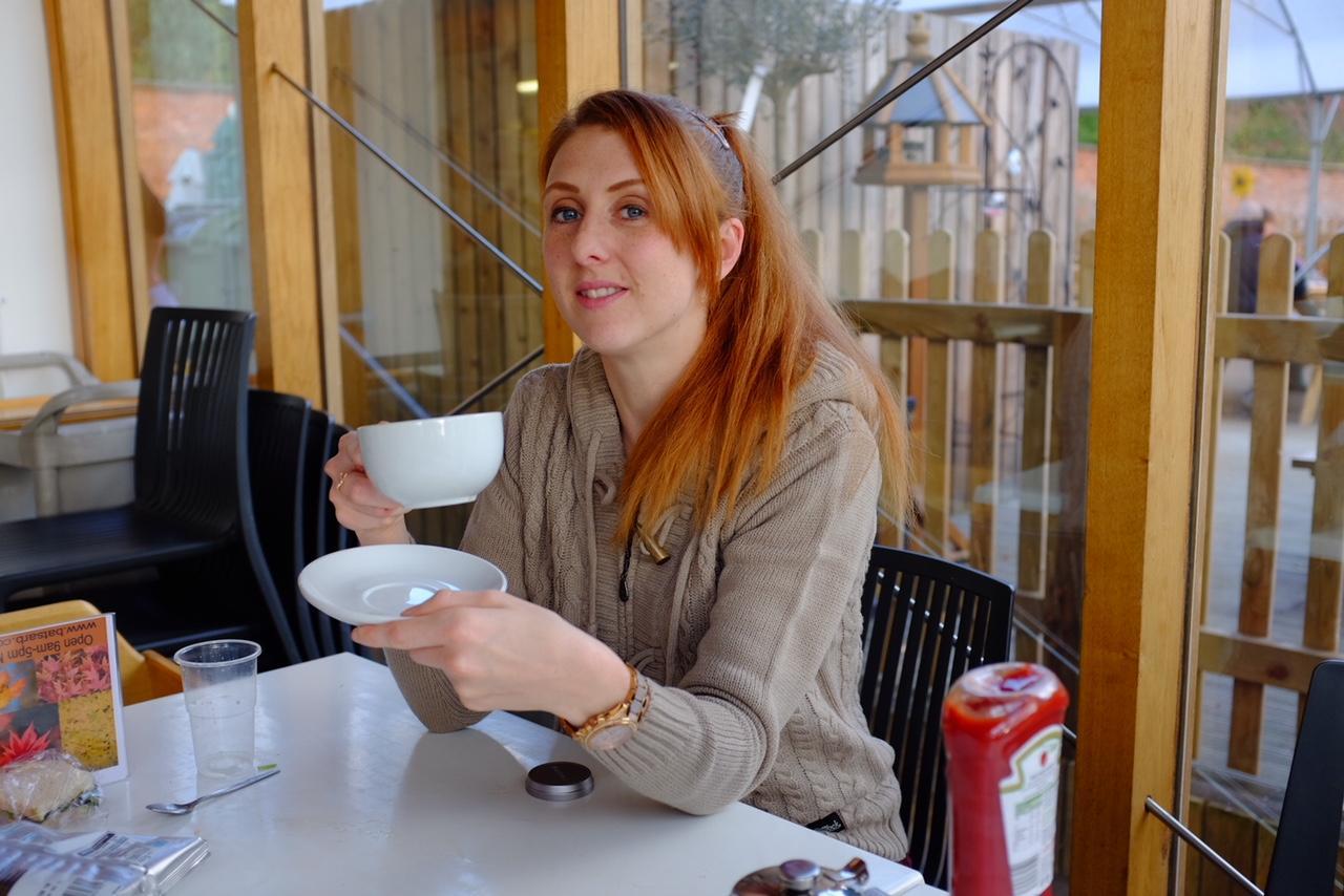 redhead sat in cafe in Saltrock knit drinking a hot drink