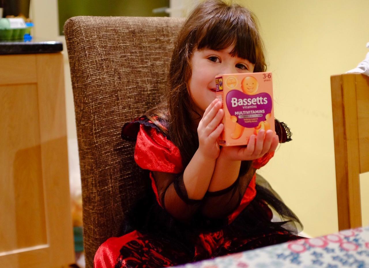 girl holding Bassetts multivitamins