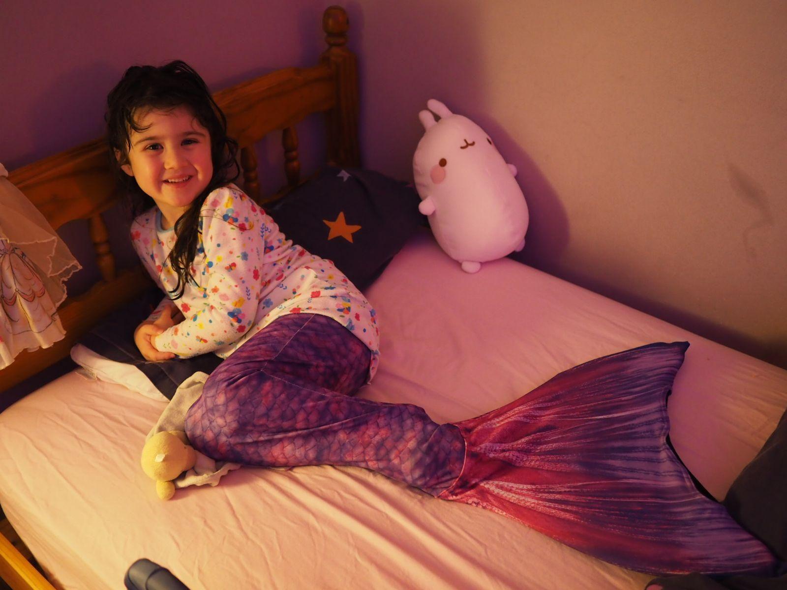 girl in purple planet mermaid tail in bed