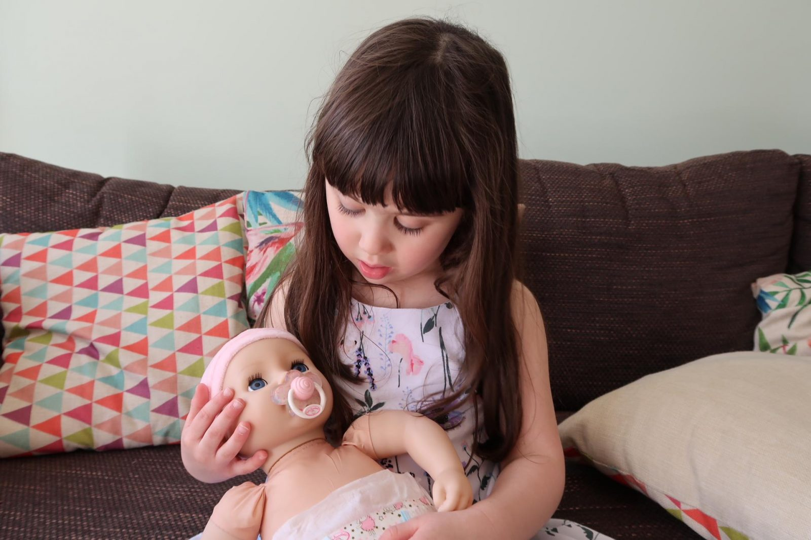 girl holding baby annabell with dummy