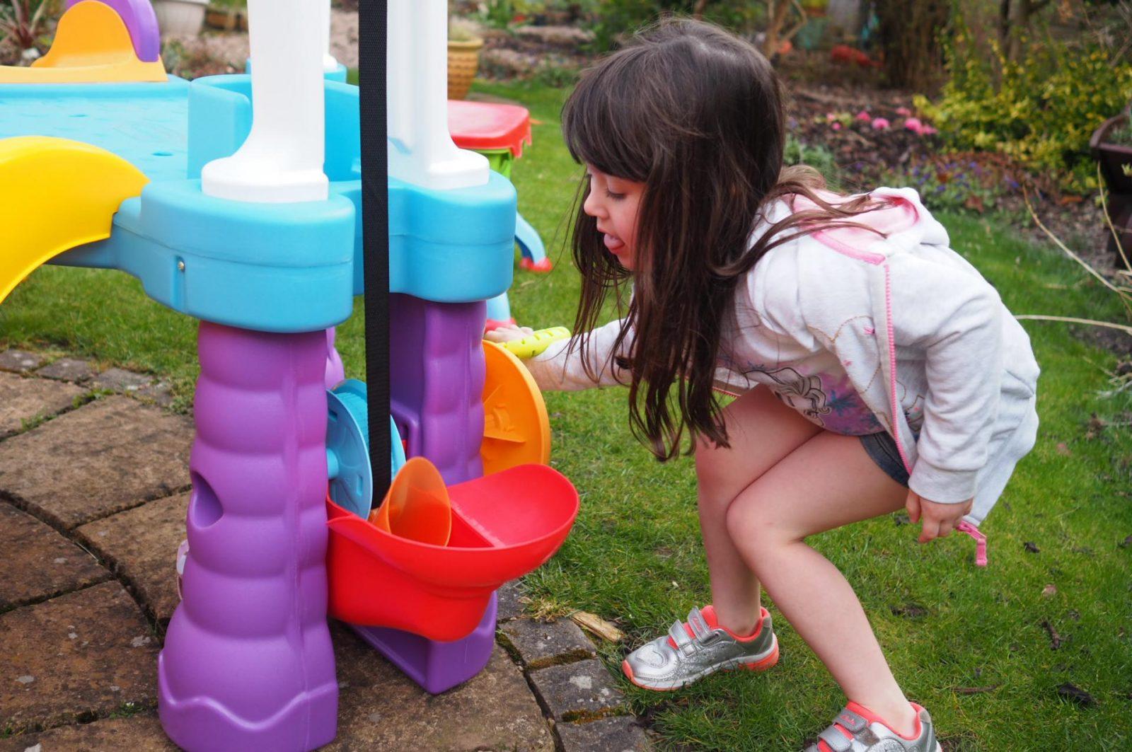 girl using conveyor belt on Little Tikes Tumblin' Tower