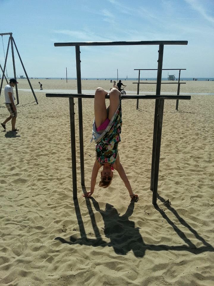 girl hanging upside down on muscle beach