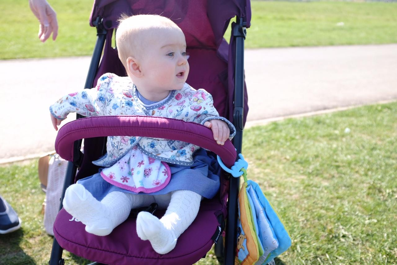 baby in the Joie Nitro LX Stroller in mulberry