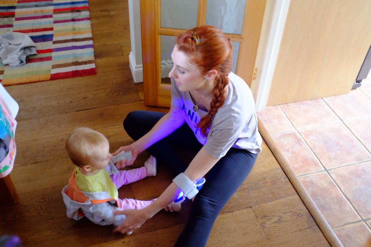 girl with baby. girl wearing philips blue control on elbow for psoriasis