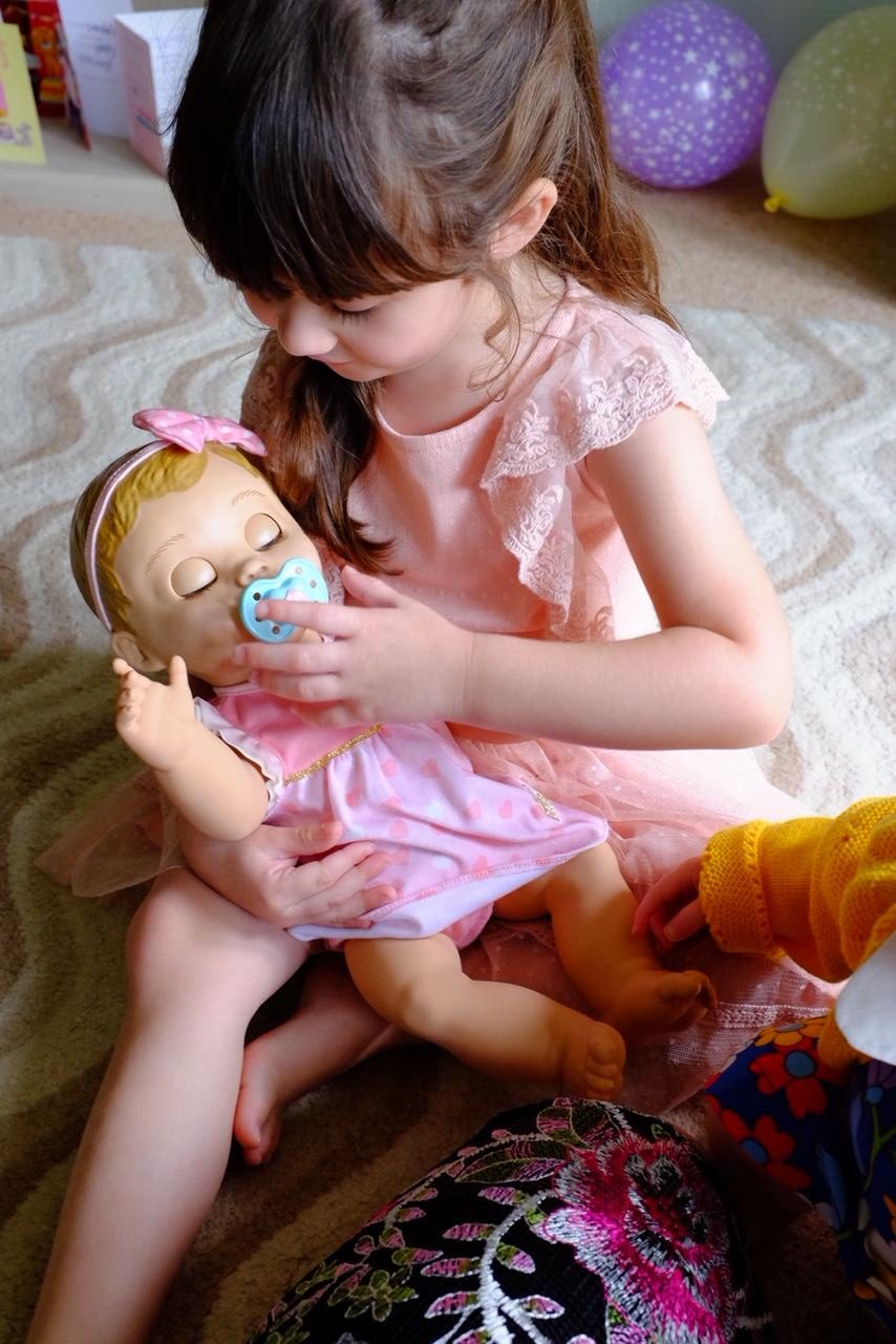 girl soothing luvabella doll with dummy