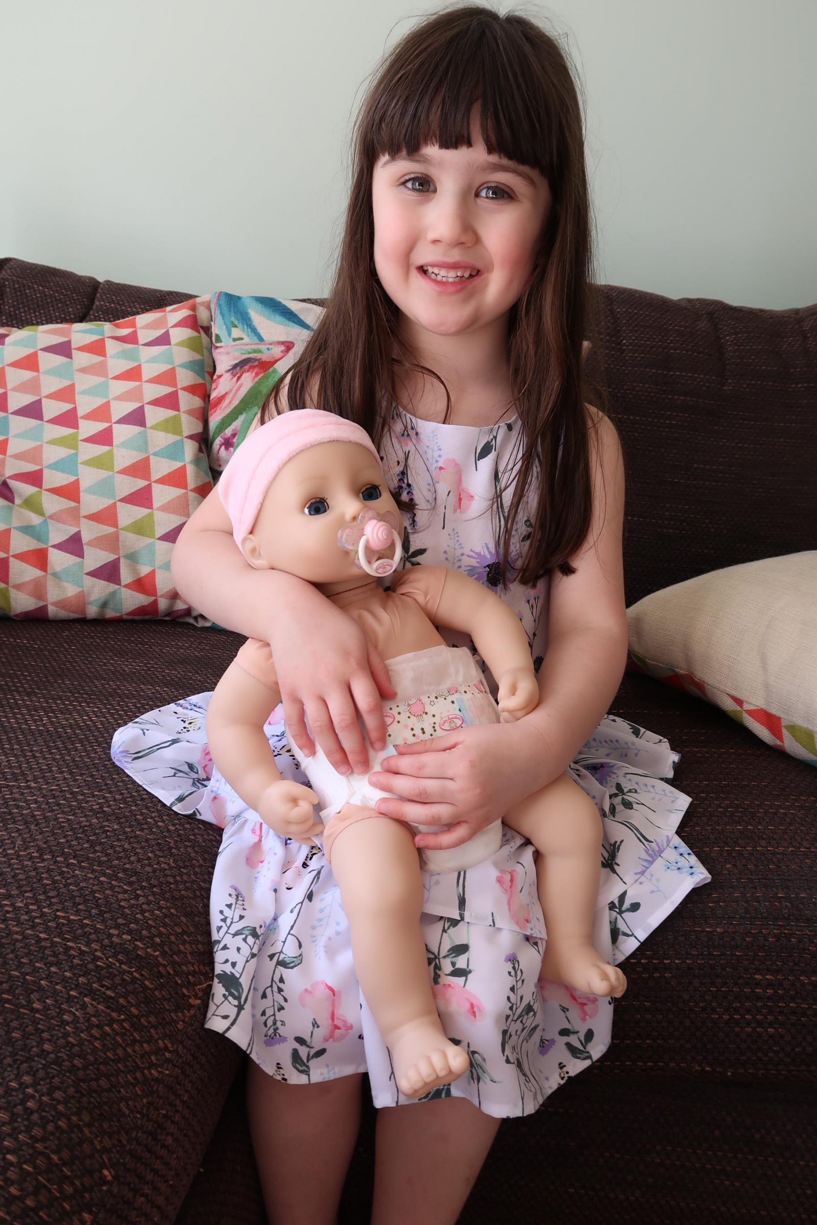 child holding interactive baby annabell