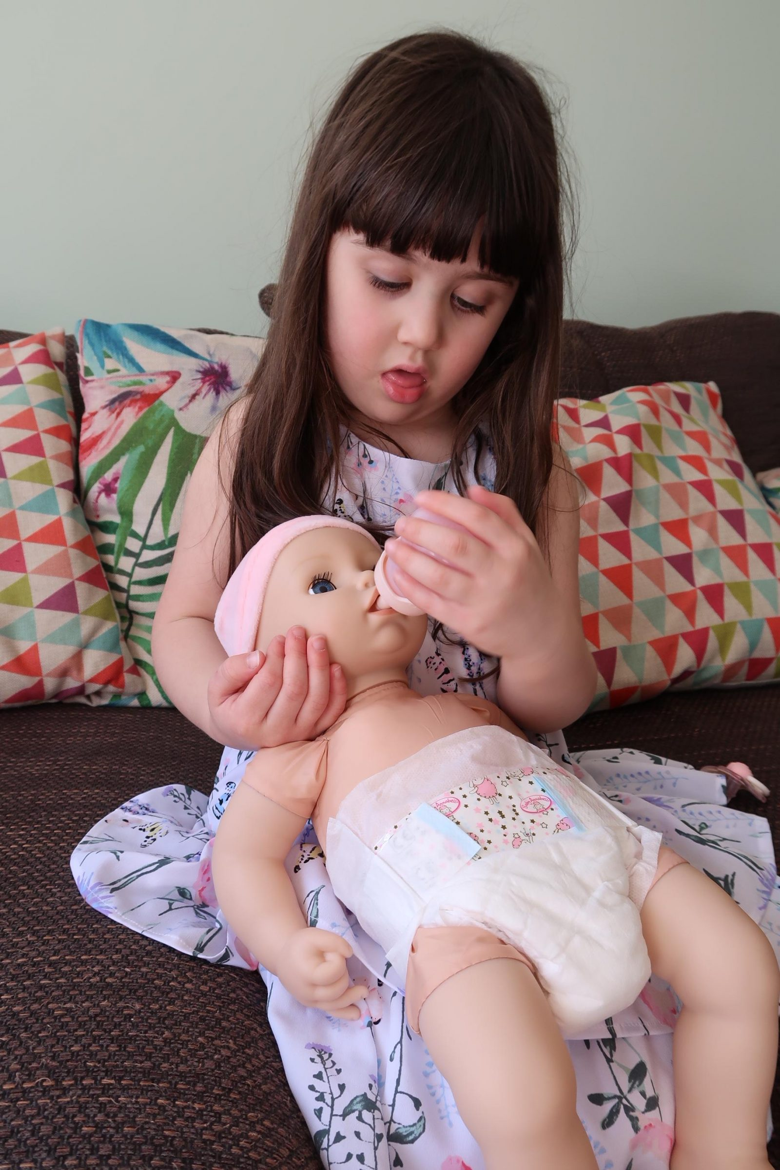 girl feeding interactive baby annabell doll with bottle