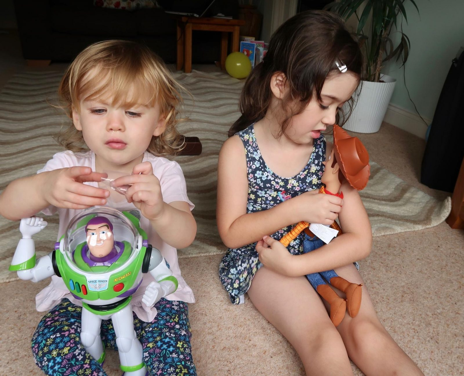 girls platying with smyths toys buzz and woody