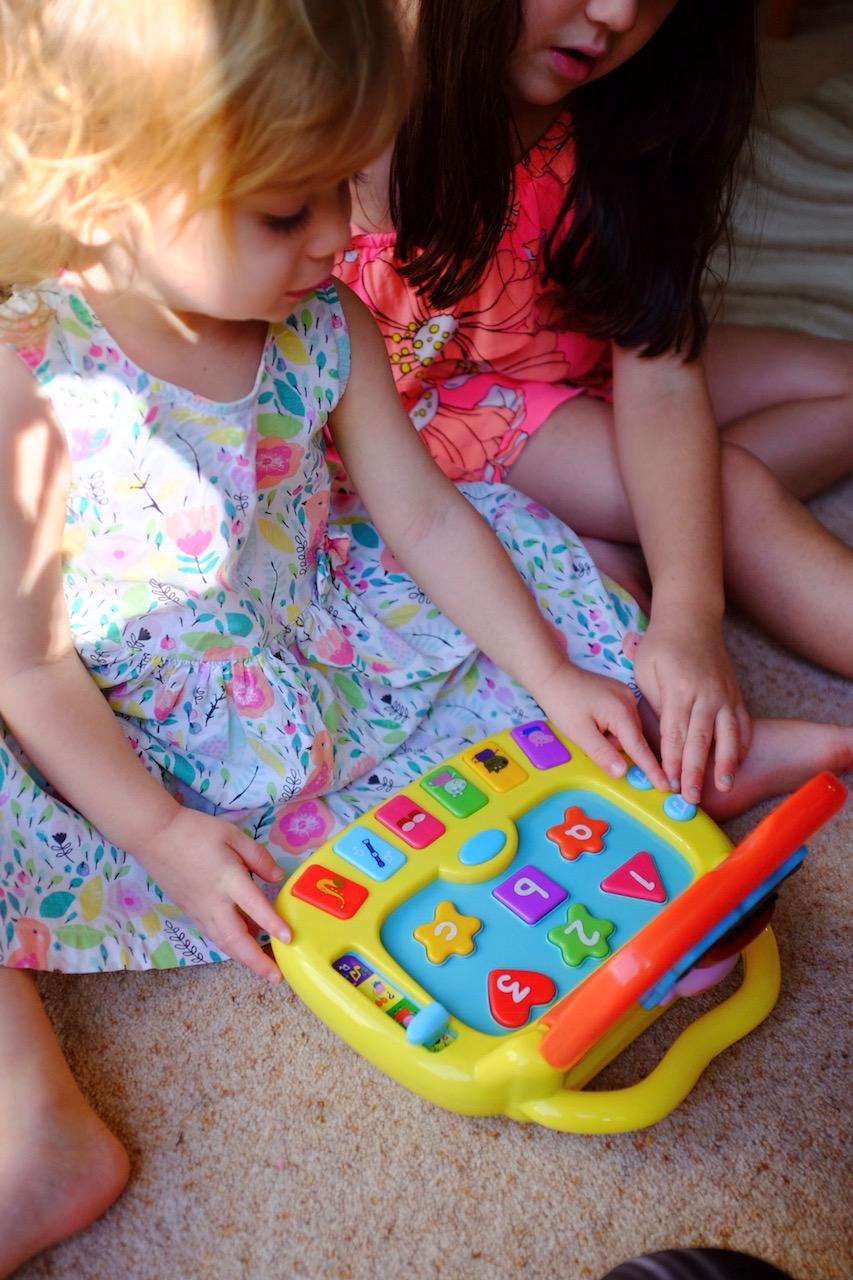 sisters playing with Peppa Pig Laugh and Learn Laptop