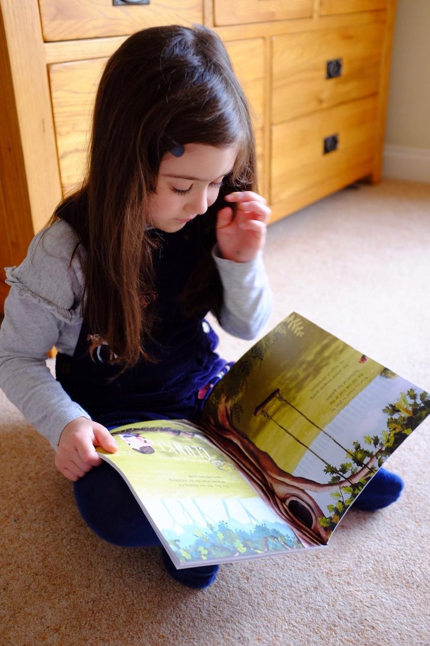 Girl reading Librio The Tree, The Key and Me Book