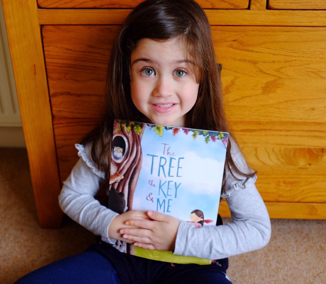 Girl holding Librio The Tree, The Key and Me Book