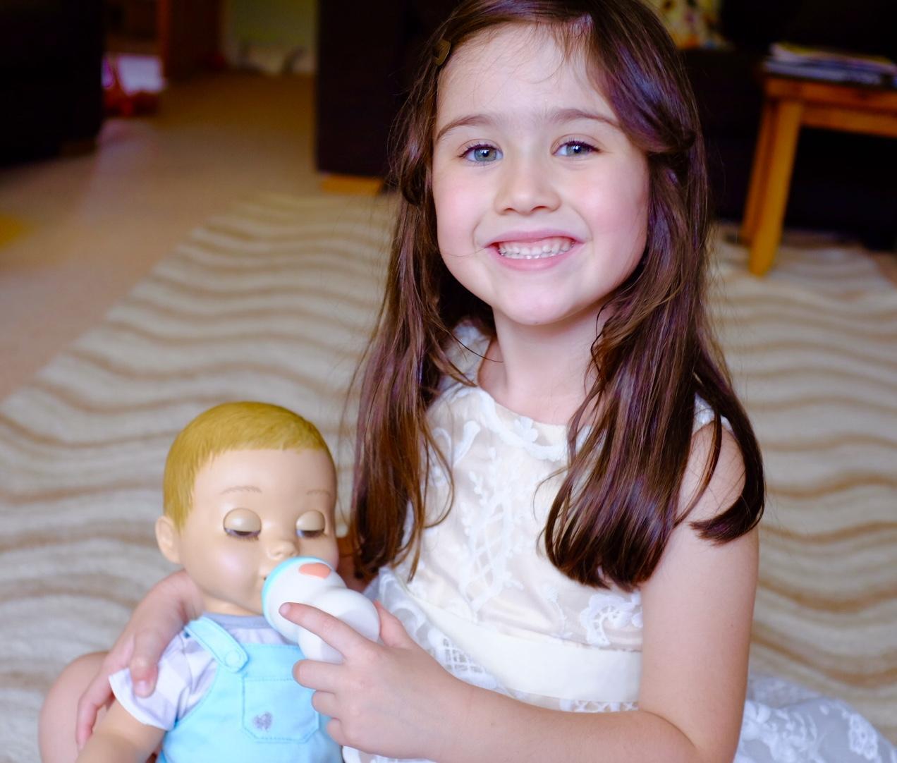 girl feeding Luvabeau doll with bottle
