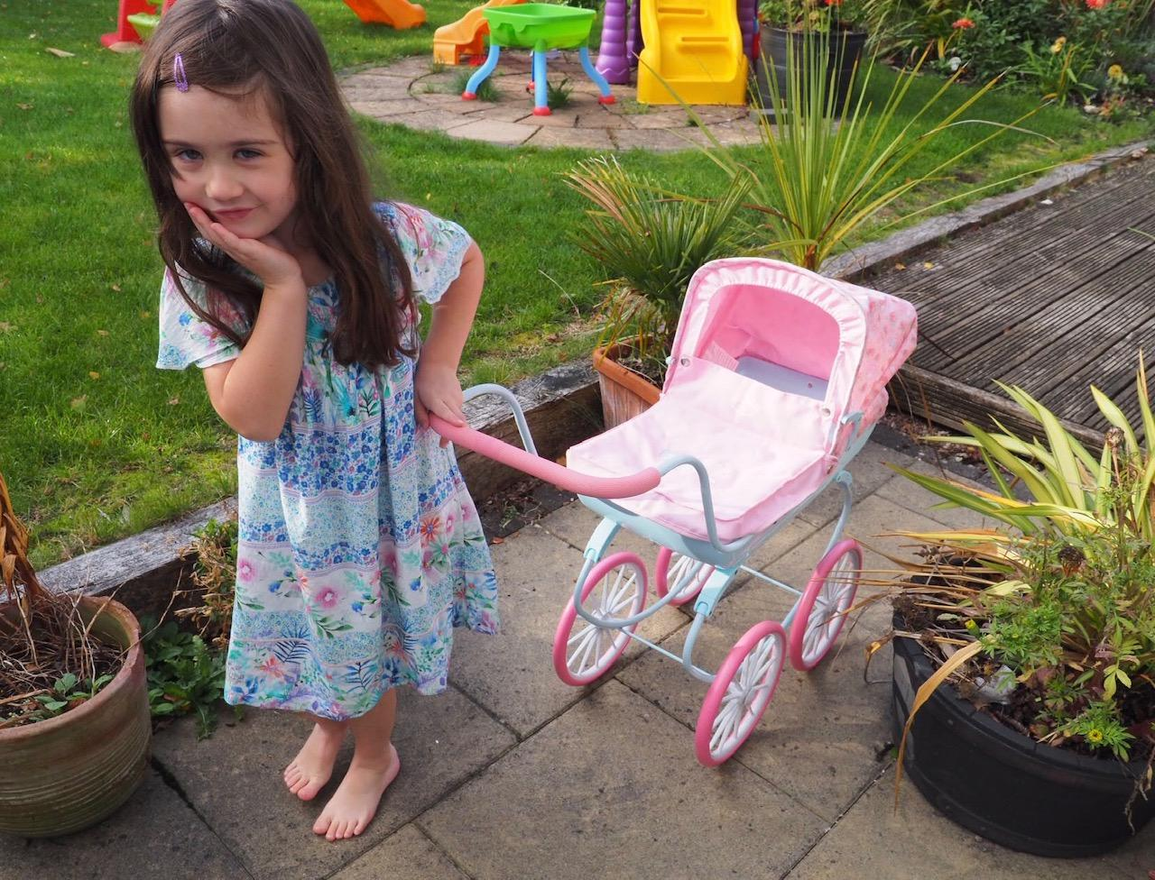 girl pushing the baby annabell carriage pram