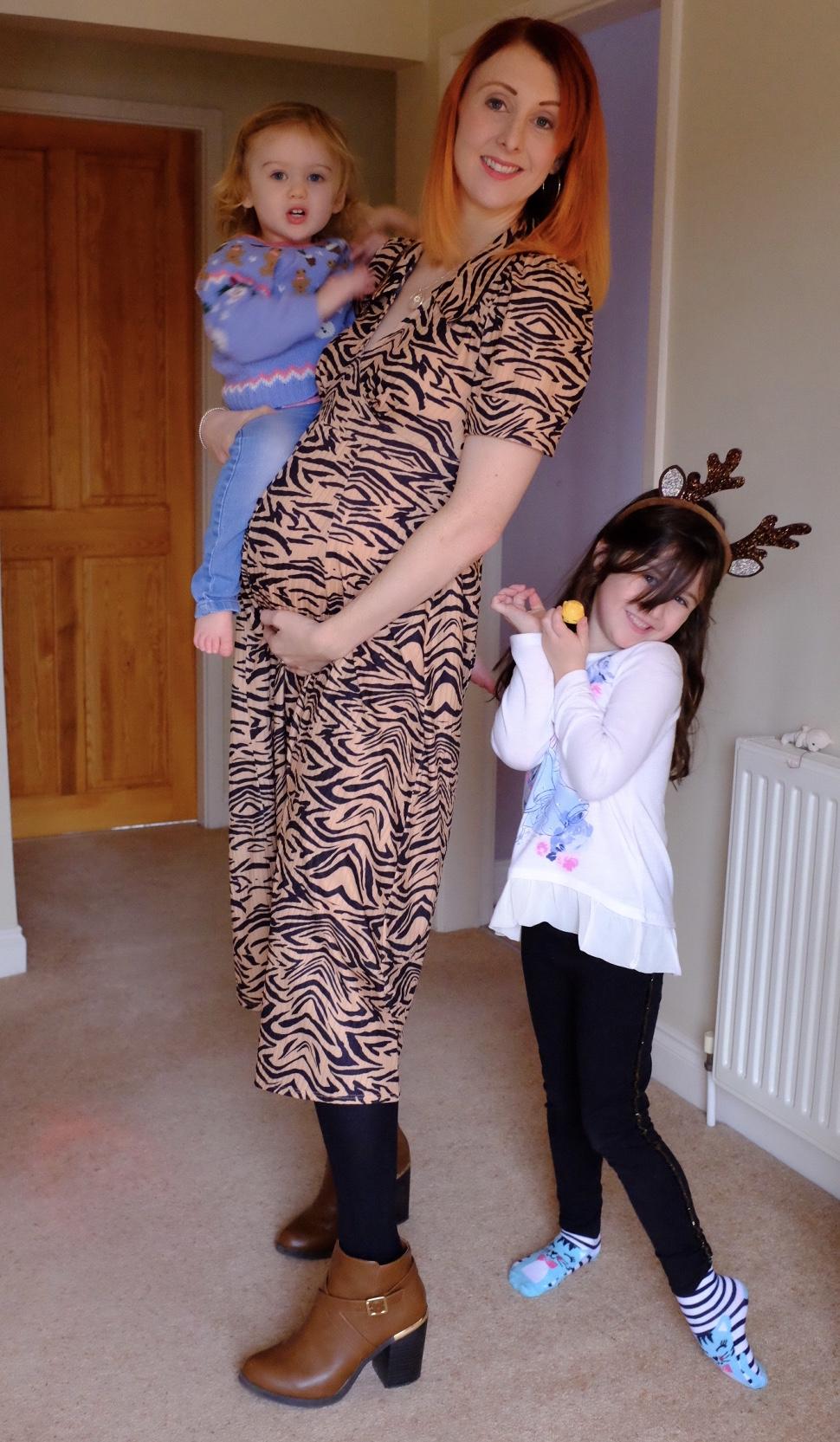 girl in maternity long animal print dress