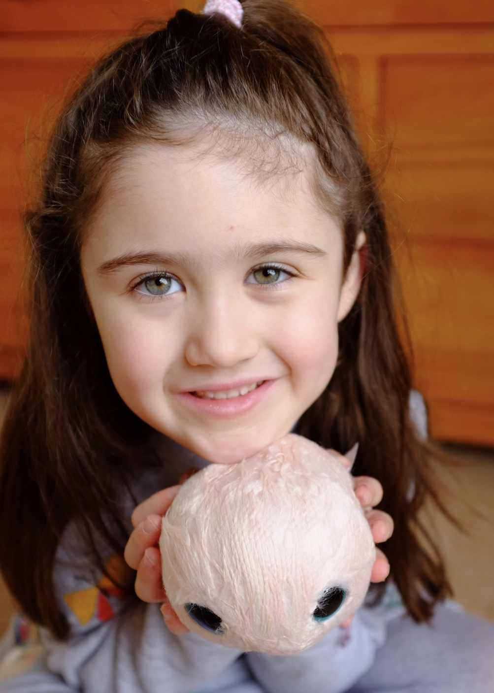 Girl holding pink Blossom Bunnies Scruff a Luvs ball before washing