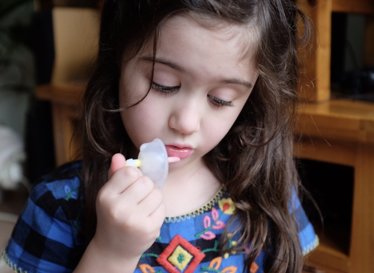 girl testing out num noms sparkle smoothies lip gloss
