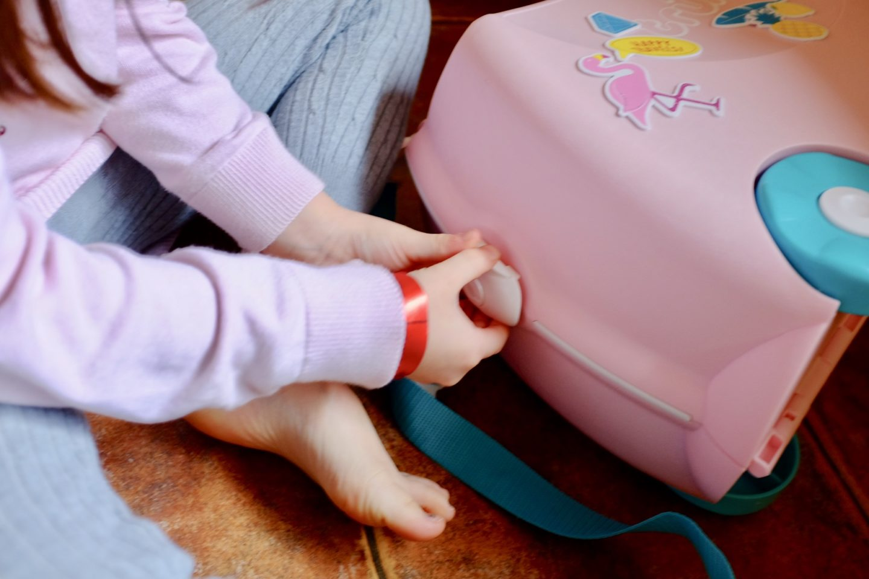 girl opening Flossi the Flamingo Trunki