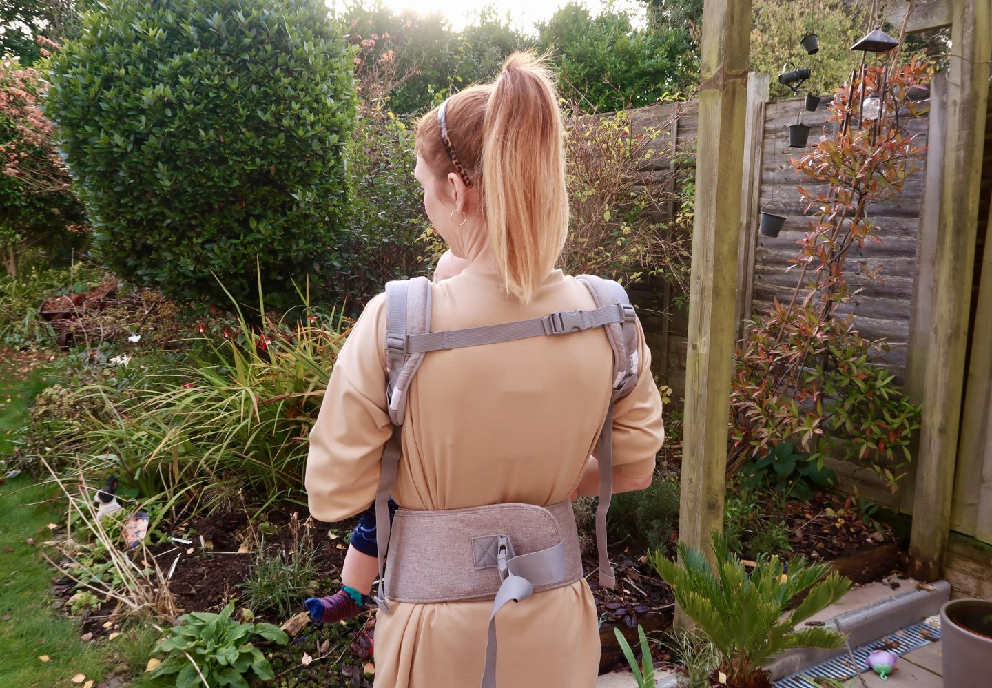 girl with lictin baby carrier straps from behind