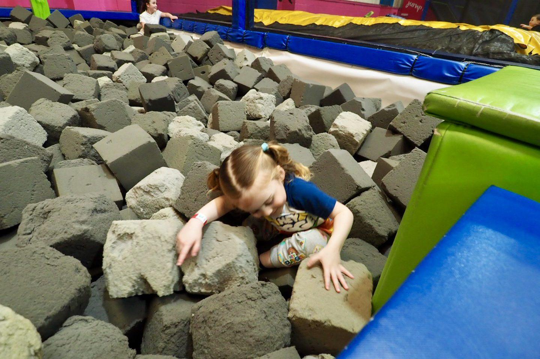 girl climbing out of foam blocks
