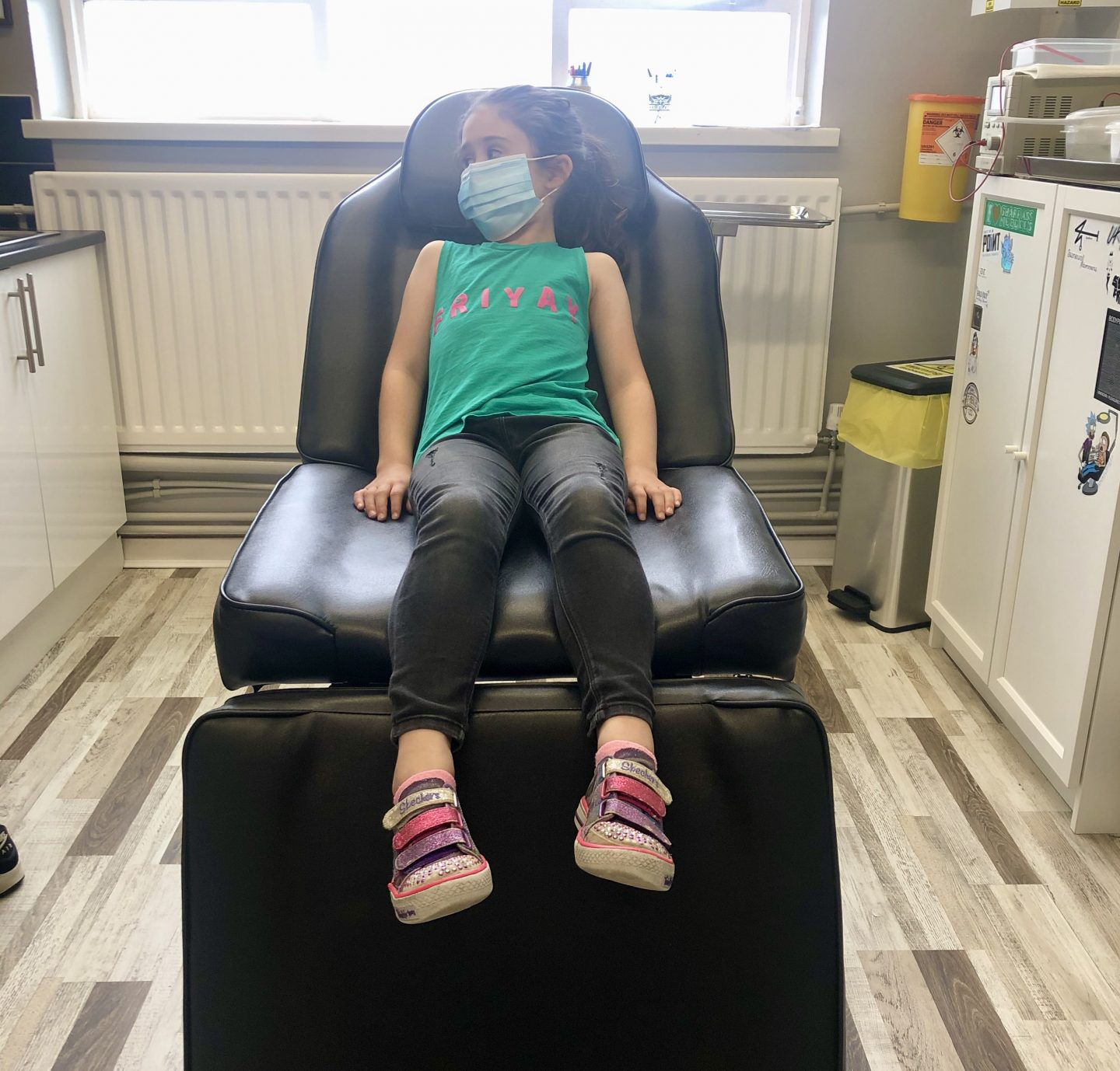 girl in chair waiting for kids ears pierced with a needle