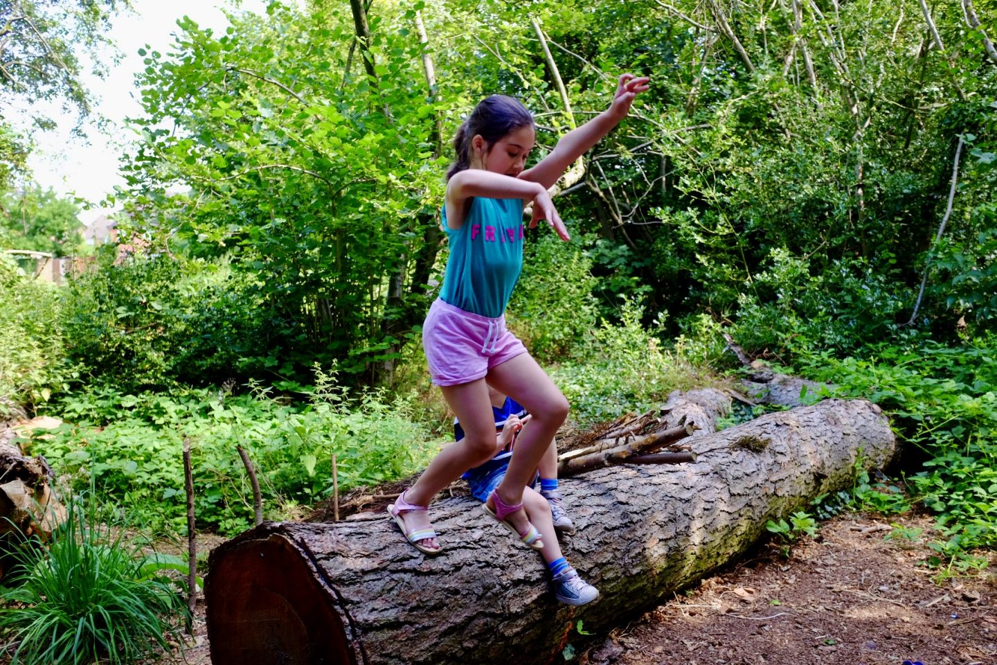 girl jumping off a log - outdoor learning