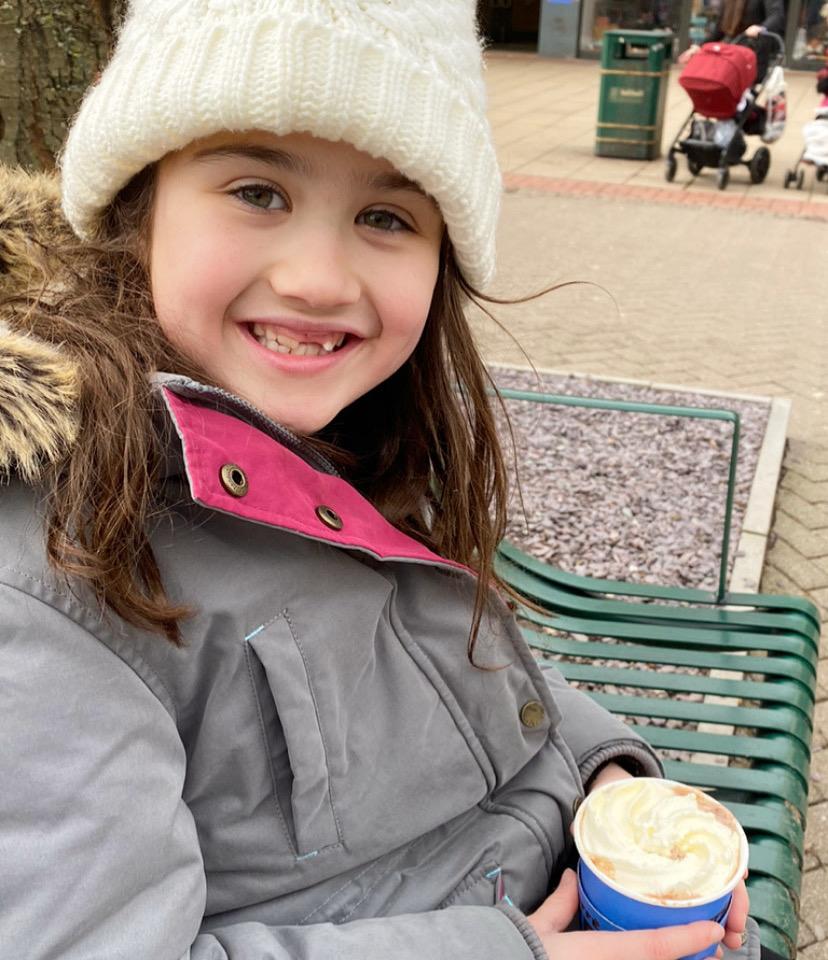 girl sat outside in her coat