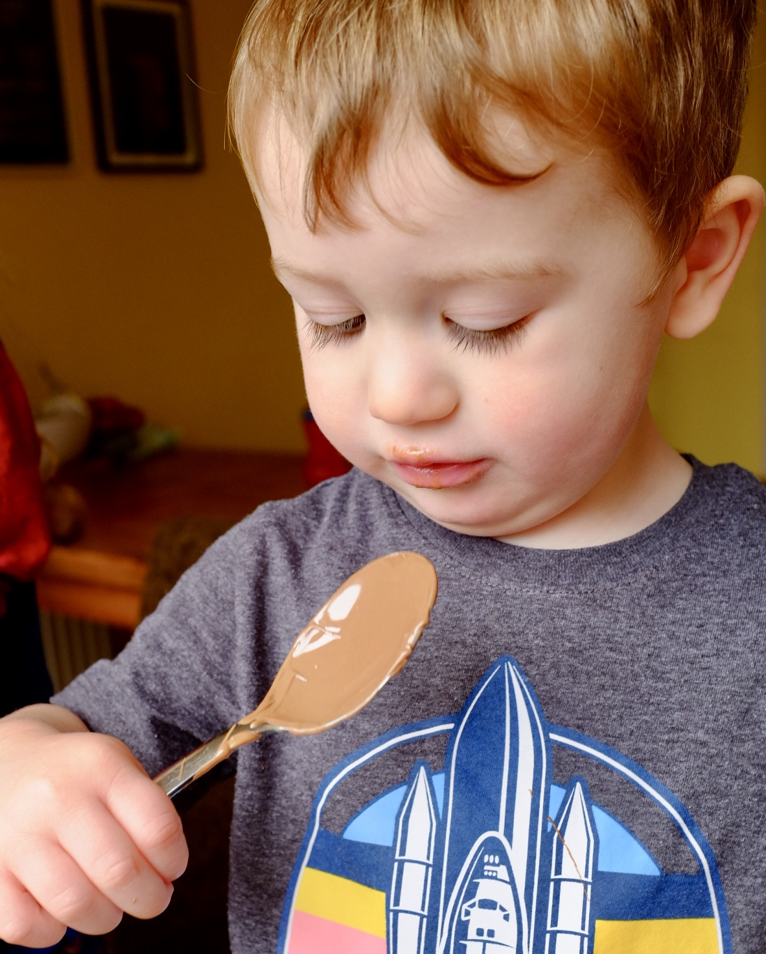 Little boy licking a chocolate spoon