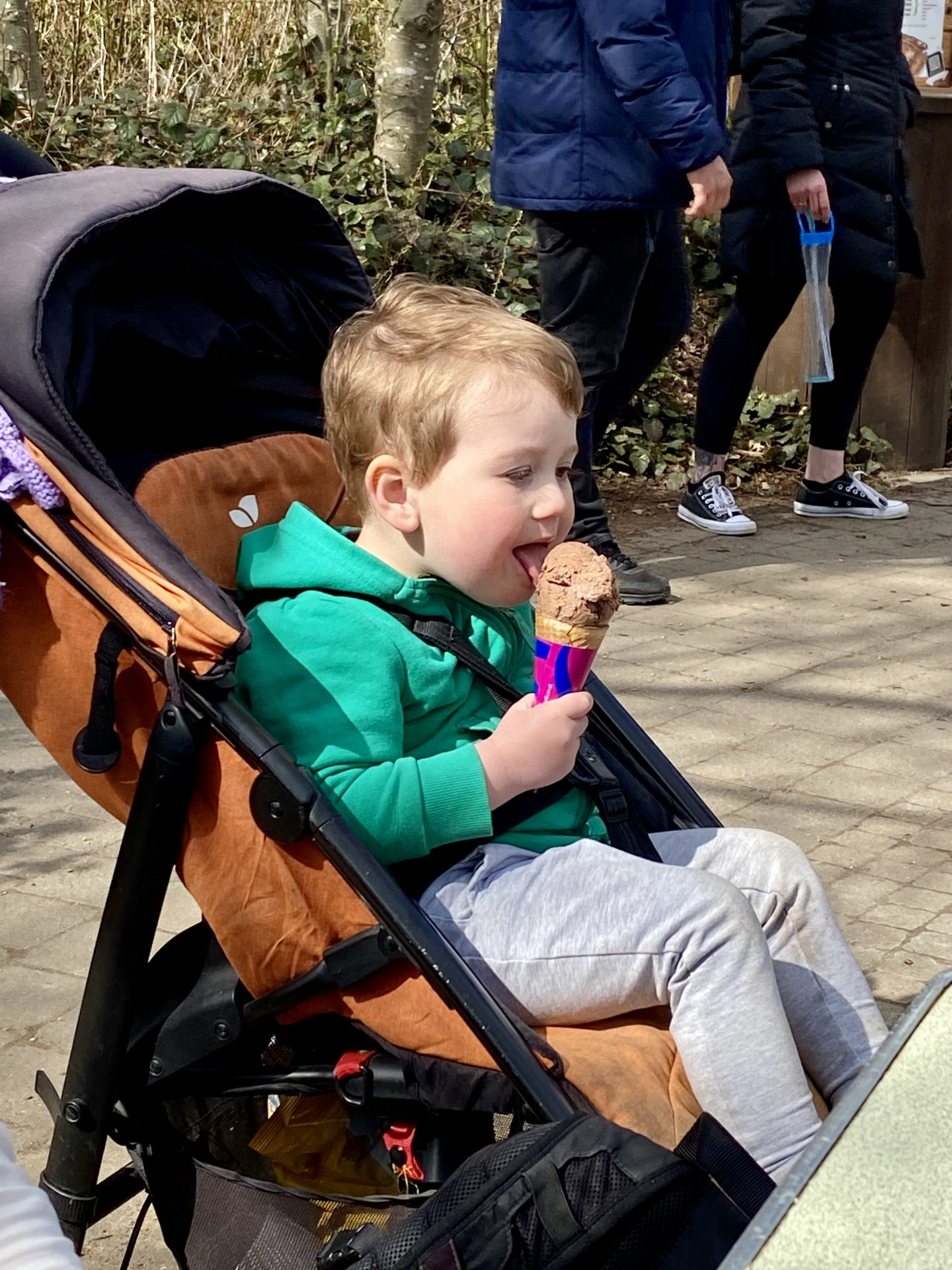 toddler eating an ice-cream in a buggy