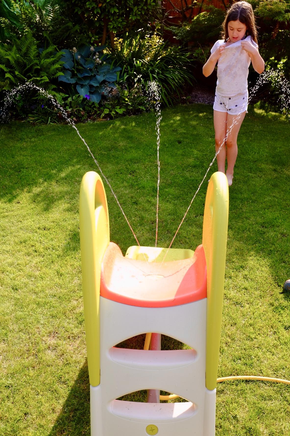 girl getting wet from the Smoby KS slide spray