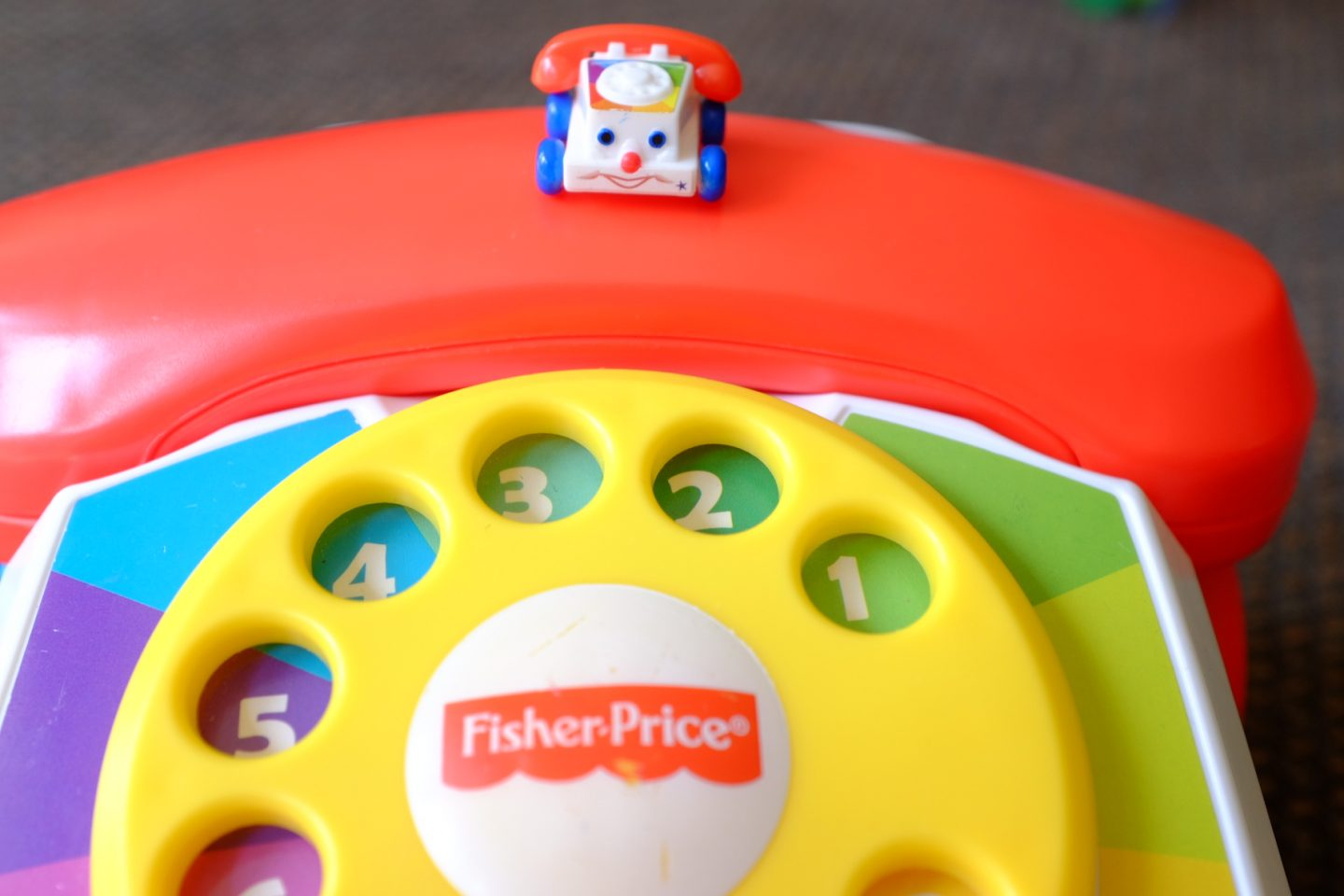 Micro toy fisher price phone miniature on top of a large one